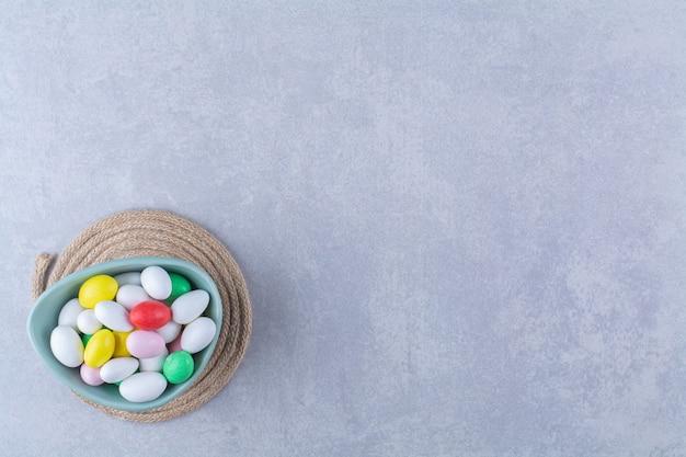 Синяя глубокая миска, полная разноцветных бобовых конфет на серой поверхности