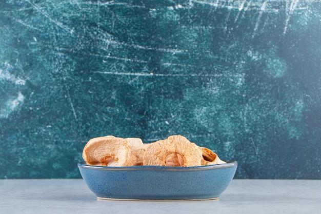 돌 배경에 건강에 좋은 말린 사과가 있는 파란색 깊은 접시.
