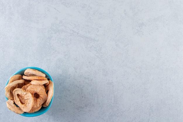 대리석 배경에 건강한 말린 과일이 있는 파란색 깊은 접시.