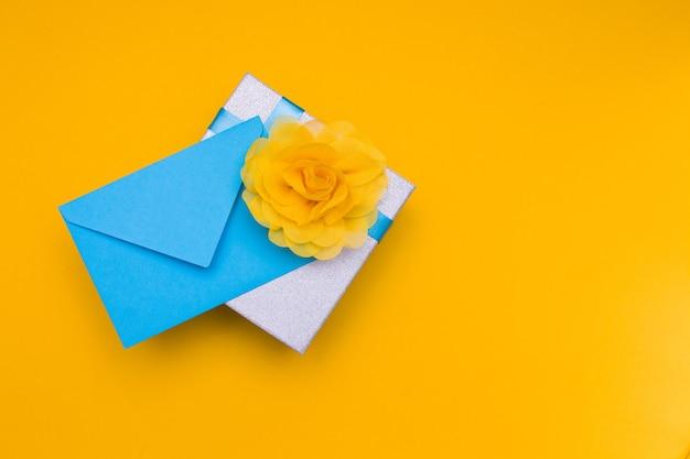 Синий конверт и подарочная коробка на желтом фоне, копией пространства, вид сверху