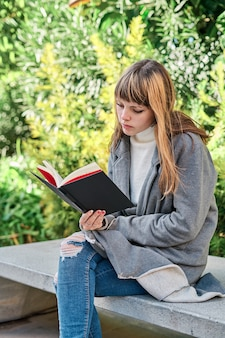 Голубоглазая кавказская белокурая молодая женщина читает книгу в парке