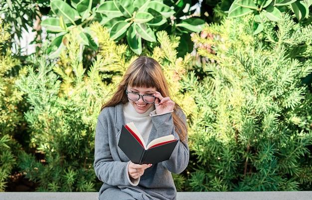 Голубоглазая кавказская блондинка молодая женщина в очках читает книгу в парке