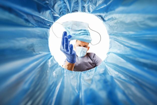 Мужчина в синей перчатке выбрасывает использованную медицинскую маску в мусор, вид из ведра. концепция утилизации медицинских отходов и последствия защиты от распространения вирусов