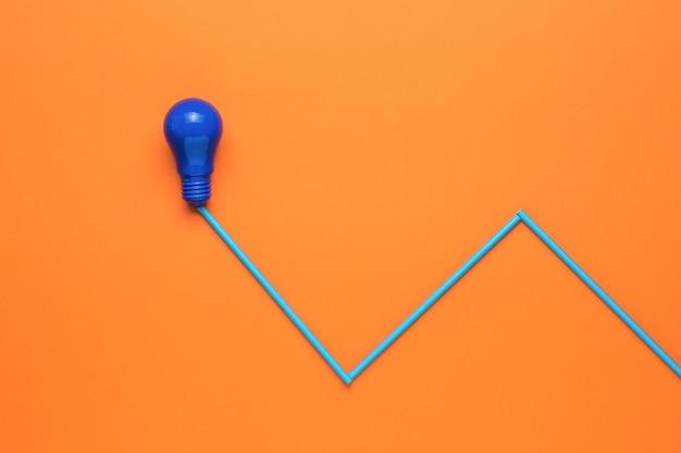 青いランプとオレンジ色の背景に接続されたワイヤーの模倣。ミニマリズム。エネルギーとビジネスの概念。フラットレイ。