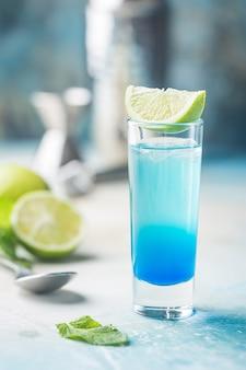 青い背景の上にライムと青い層のアルコールカクテル