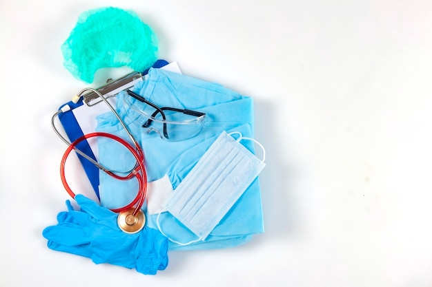 青い医療用ガウンの帽子の安全メガネ聴診器と患者カード付きクリップボード