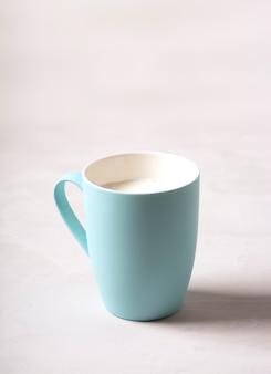 На сером бетонном столе стоит синяя кружка с молоком.