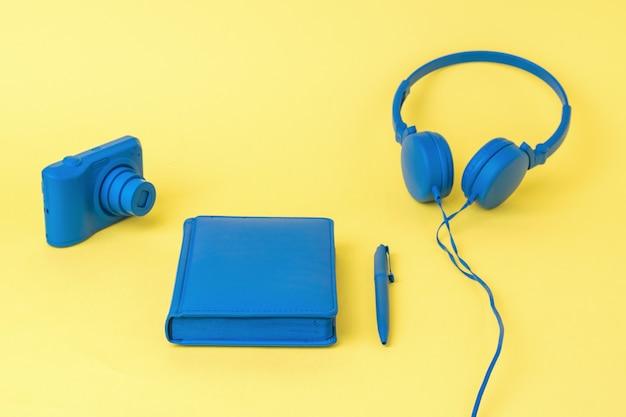 Синий блокнот, наушники и фотоаппарат на желтой поверхности. стильный дизайн рабочего места.