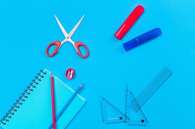 Синяя тетрадь с черными кольцами лежала на синем с карандашами для рисования, красными ножницами, розовой точилкой, прозрачными линейками и двумя красными и синими маркерами.