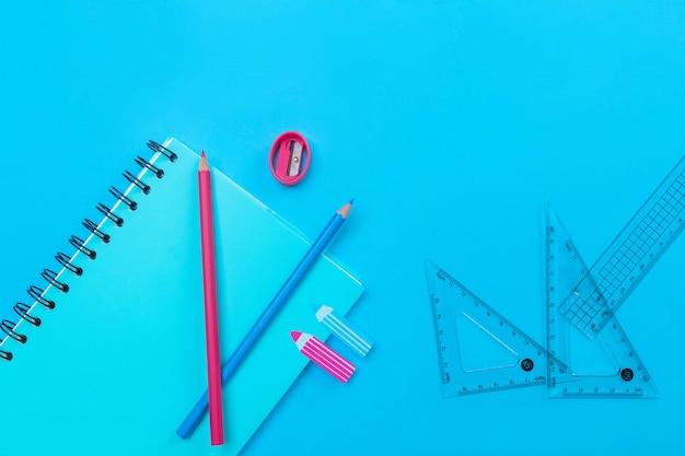 Синяя тетрадь с черными кольцами лежала на синем с рисунком карандашами, наклейками, розовой точилкой, прозрачными линейками и двумя красными и синими маркерами.