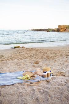 海岸にコーヒー、バッグ、帽子が付いたプラスチック製のグラスが置かれた青い格子縞。