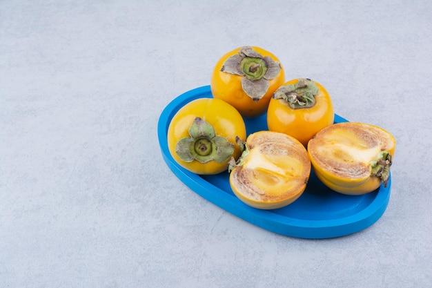 白い背景に新鮮な柿でいっぱいの青いプレート。高品質の写真