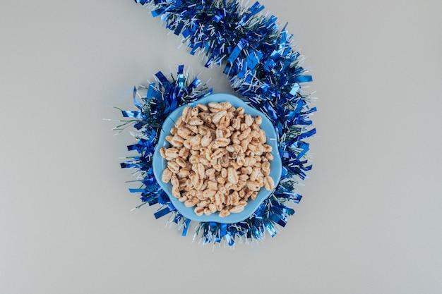 크리스마스 화 환과 건강 한 곡물의 전체 파란색 접시.
