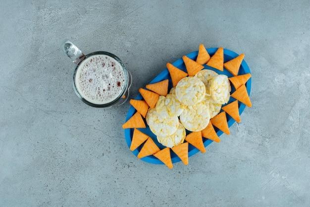 맥주 한 잔과 바삭한 칩의 파란색 접시. 고품질 사진