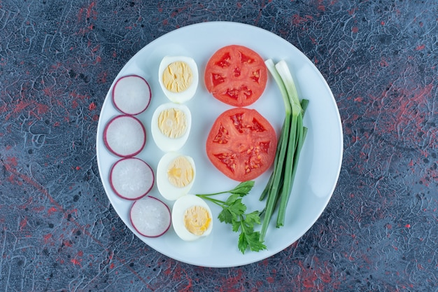야채와 함께 삶은 계란의 파란색 접시입니다.