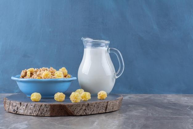 木の部分にミルクのガラス瓶と健康的な甘いコーンフレークの青いプレート。