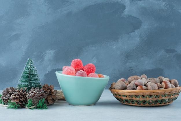 Голубая тарелка мармелада с маленькими рождественскими шишками на мраморном фоне. фото высокого качества