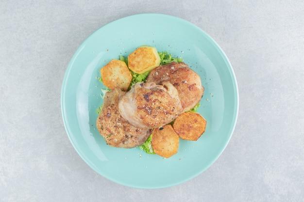 Голубая тарелка мяса с жареным нарезанным картофелем и листьями салата.