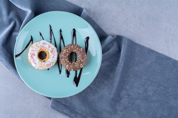 다채로운 스프링클과 함께 두 개의 달콤한 도넛의 파란색 접시.