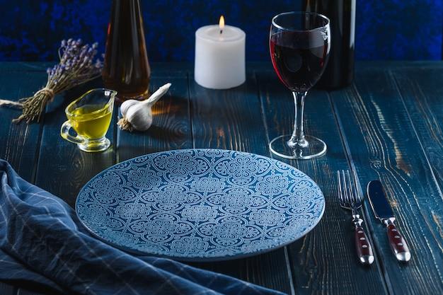 木製のテーブルにワインとバターの青いプレート。食べ物を待っています。素朴なスタイル。