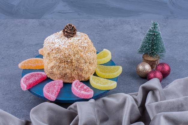 Синяя тарелка с восхитительным пирогом и сладкими желейными конфетами