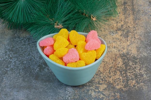 심장 모양의 설탕 젤리 사탕과 파란색 접시. 고품질 사진