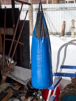 青いサンドバッグがオープンガレージにぶら下がっています。あらゆるタイプの人々のためのスポーツ活動