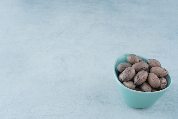 Голубая тарелка, полная орехов на мраморном фоне. фото высокого качества