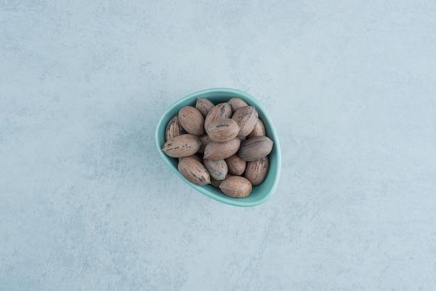 大理石の背景にナッツでいっぱいの青い小皿。高品質の写真