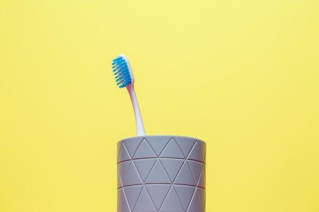 파란색 칫솔이 회색 유리에 서 있습니다. 치과 치료 개념