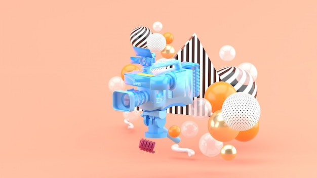 ピンク色のカラフルなボールに囲まれた青いビデオカメラ。 3dレンダー