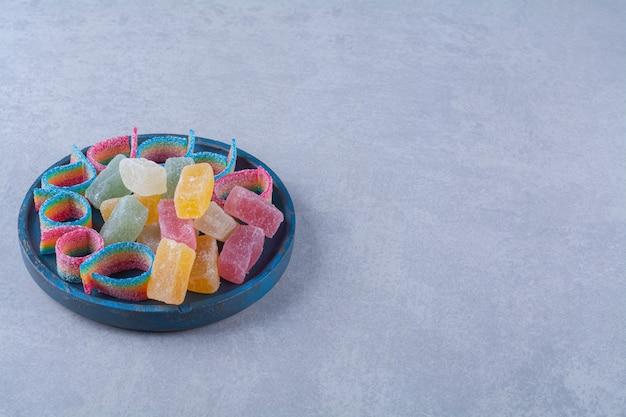 다채로운 설탕 마멀레이드로 가득한 파란색 나무 보드