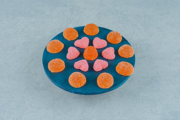 Синяя деревянная доска, полная оранжевых сладких желейных конфет с желейными конфетами в форме сердца