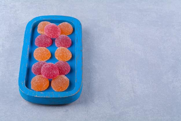 빨간색과 주황색 설탕 마멀레이드가 가득한 파란색 나무 보드