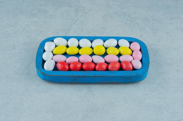 흰색 표면에 둥근 달콤한 다채로운 사탕으로 가득한 푸른 나무 보드