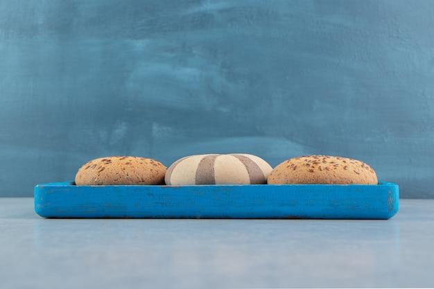 甘いクッキーがいっぱいの青い木の板。