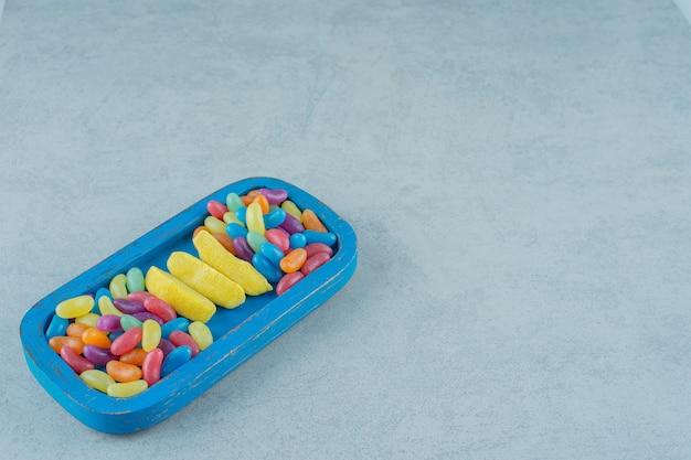 Синяя деревянная доска жевательных конфет в форме банана с красочными бобовыми конфетами