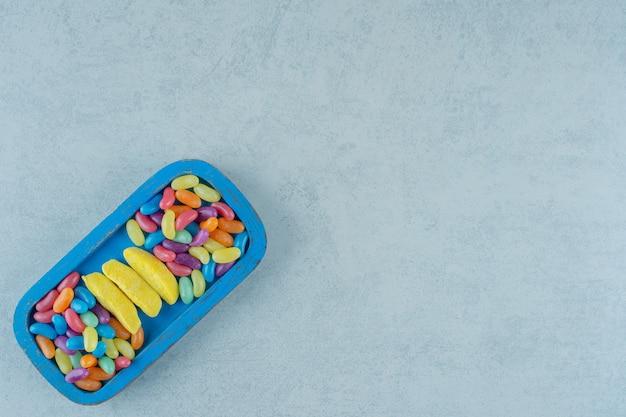 다채로운 콩 사탕과 바나나 모양의 씹는 사탕의 푸른 나무 보드