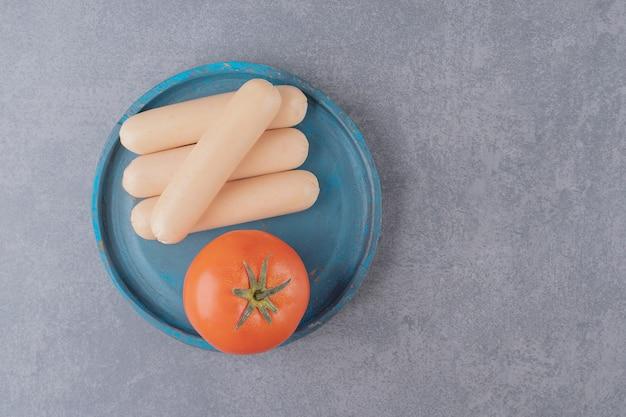 赤いトマトとゆでソーセージの青い木の板。