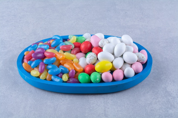 カラフルな甘いジェリービーンズキャンディーの青い木の板