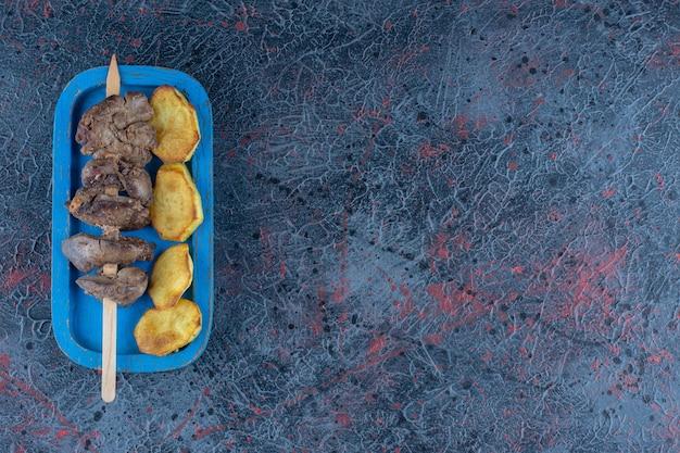 Синяя деревянная доска жареного картофеля с мясом
