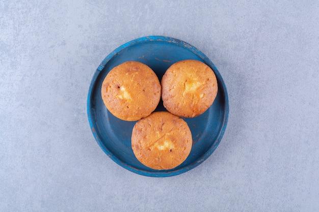 3つの甘い新鮮なカップケーキの青い木の板。
