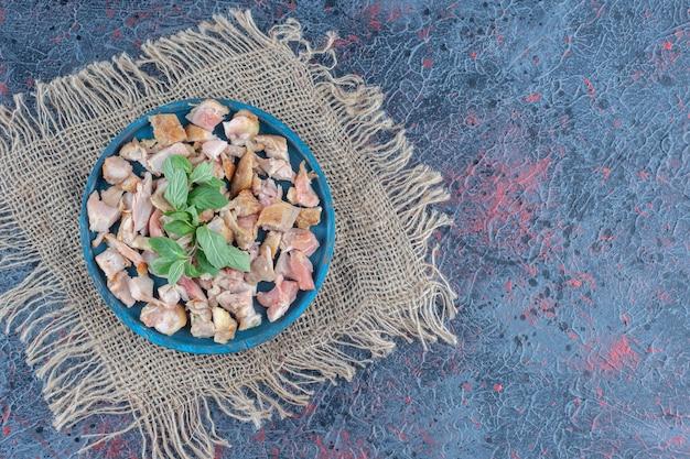 얇게 썬 닭고기와 민트가 있는 푸른 나무 판자