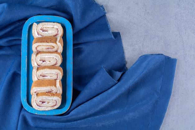 식탁보에 달콤한 얇게 썬 롤이 있는 파란색 나무 보드.