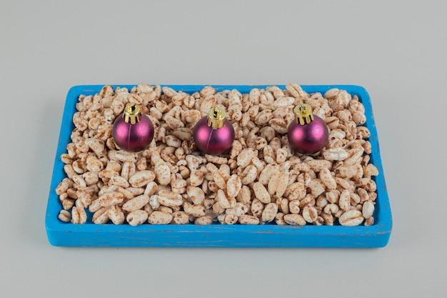 Синяя деревянная тарелка, полная здоровых хлопьев с елочными шарами.