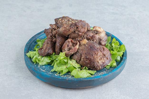튀긴 고기와 얇게 썬 양상추의 푸른 나무 접시입니다.