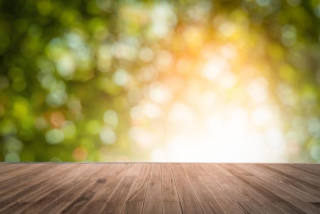 木製の表面とぼやけている自然な日光の背景