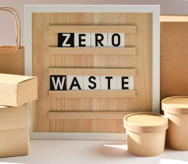 Доска с надписью нулевые отходы с бумажным пакетом и одноразовыми контейнерами