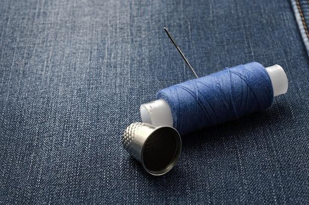 針と指ぬきが付いた糸のボビン。デニムの背景に。