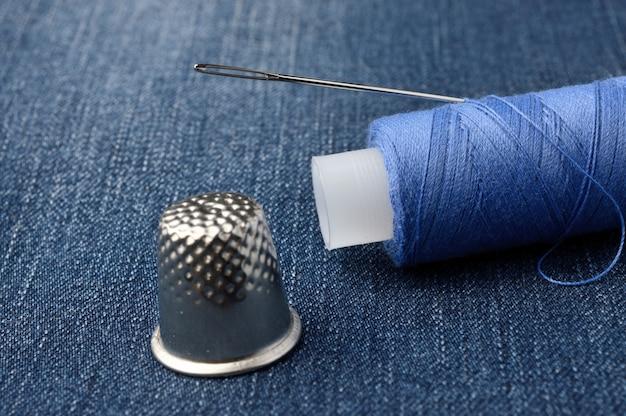 針と指ぬきが付いた糸のボビン。デニムの背景に